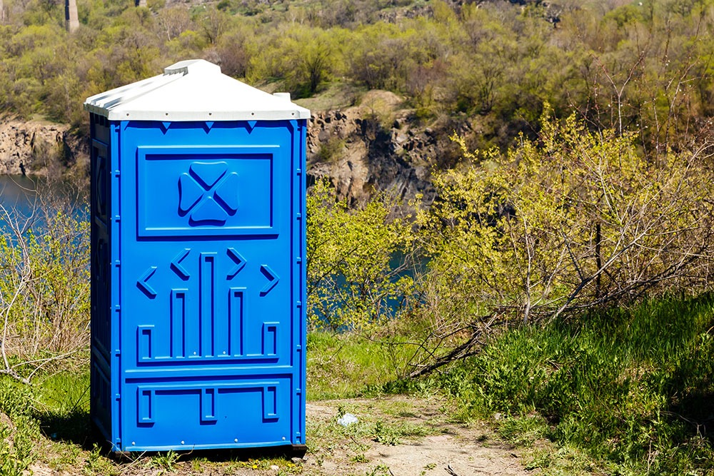 Blue cabine bio toilet mountain park sunny summer day
