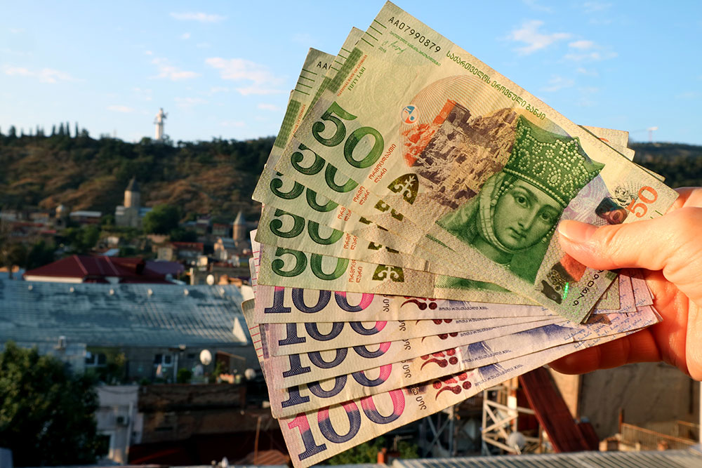 Bunch georgian 50 banknotes with blurry tbilisi city view background